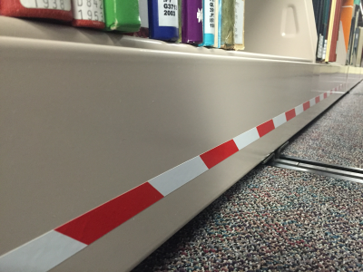 Emergency mobile range motion stop strip at bottom of shelf - touch with foot to stop shelf